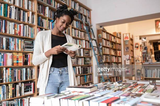 Young woman reading book at store