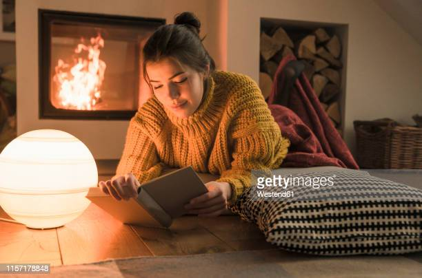 young woman reading book at the fireplace at home - cosy stock pictures, royalty-free photos & images