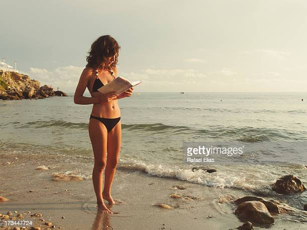 Young woman reading book at the sea shore