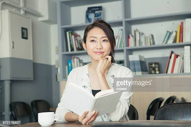 young woman reading book in café - 顎に手をやる ストックフォトと画像