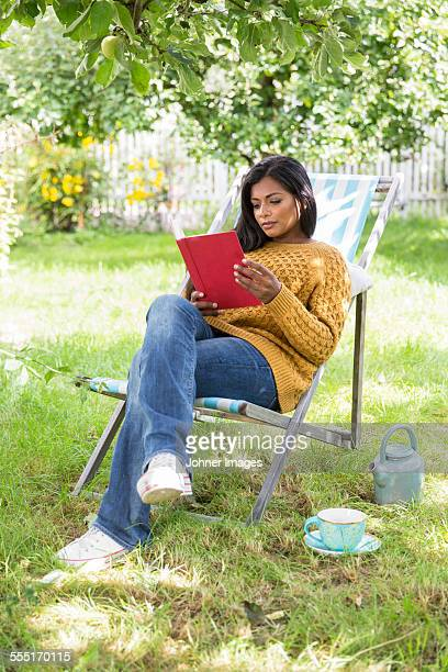 young woman reading book in garden - one young woman only stock pictures, royalty-free photos & images