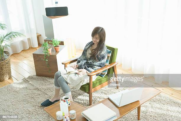 young woman reading book in room, high angle view - exclusivamente japonés fotografías e imágenes de stock