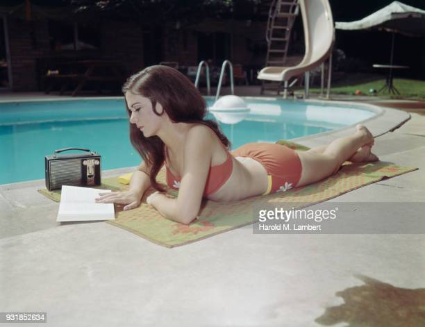 Young woman reading book near pool