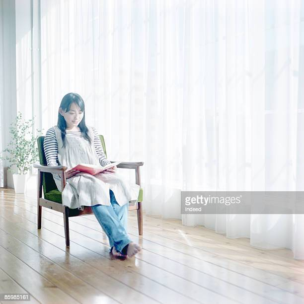young woman reading book on armchair - legs crossed at ankle stock pictures, royalty-free photos & images