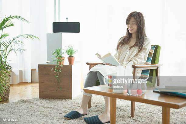 Young woman reading book on armchair