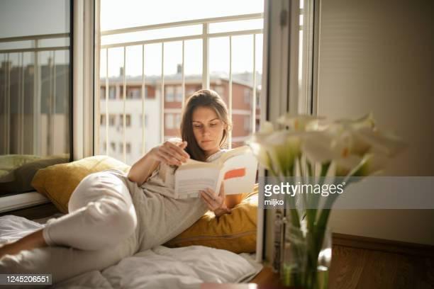 giovane donna che legge libro a letto a casa - leggere foto e immagini stock