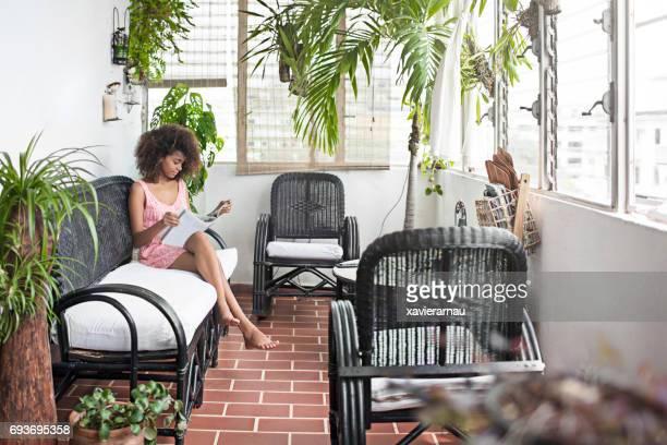 Jeune femme lisant livre sur canapé au porche