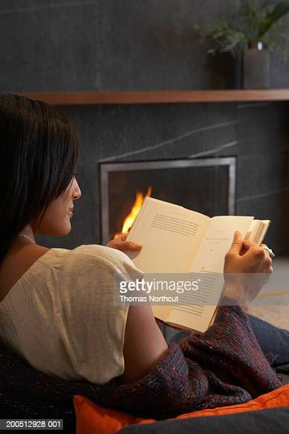 Young woman reading book on sofa, fireplace in background, rear view