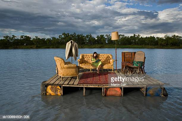 Young woman reading book on sofa on wooden raft