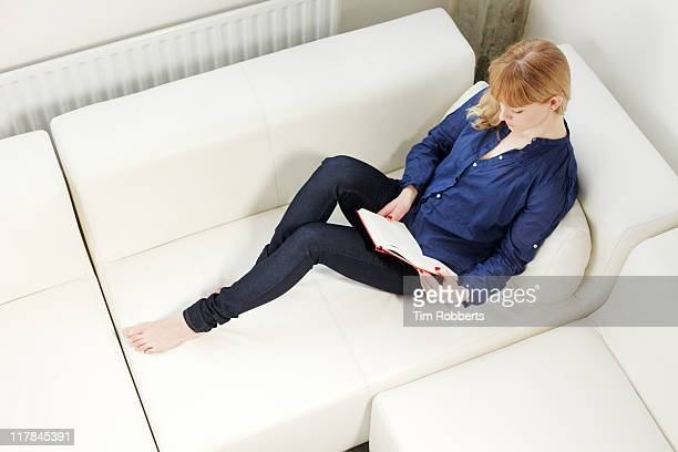 Young woman reading book on sofa.
