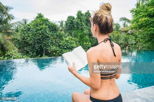 Young woman reading book on the edge of an infinity pool, Ubud, Bali
