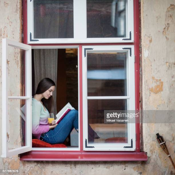 Young woman reading book on window sill