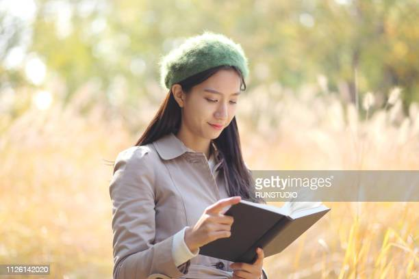 young woman reading book outdoors in autumn - トレンチコート ストックフォトと画像