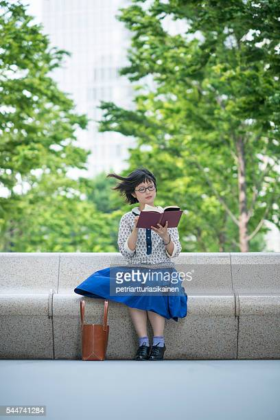 young woman reading book outdoors in windy place. - windy skirt stock photos and pictures