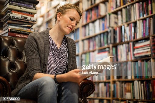 Young woman reading book sitting at bookstore