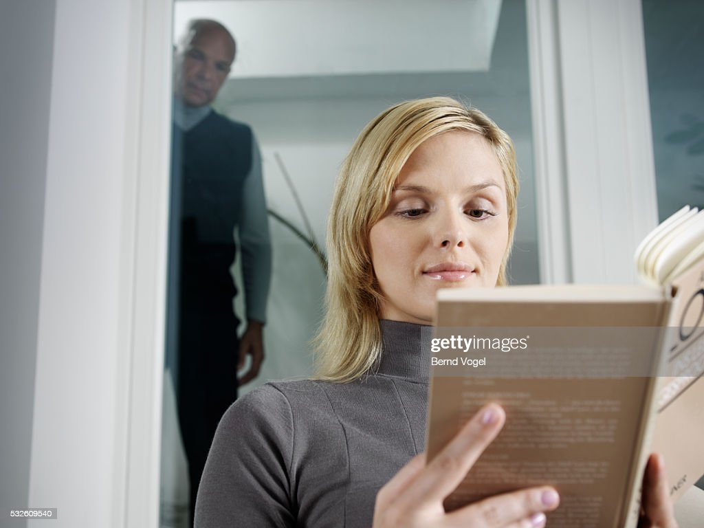 Young Woman Reading Book Watched by Senior Man : Stock Photo
