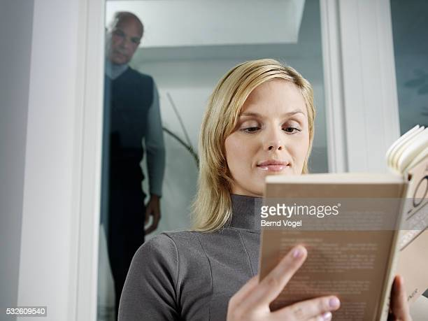 Young Woman Reading Book Watched by Senior Man