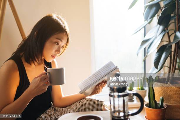 young woman reading book while drinking coffee - coffee stock pictures, royalty-free photos & images