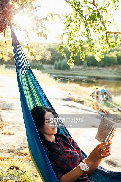 Young woman reading book while lying on hammock in forest