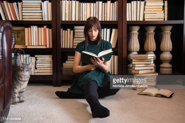 young woman reading book while sitting against bookshelf in library - lire photos et images de collection