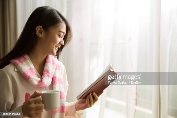 young woman reading book while sitting by window at home - torwai stock pictures, royalty-free photos & images