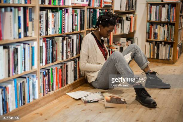 Young woman reading book while sitting on floor at bookstore