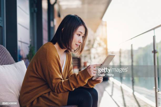 young woman reading email on digital tablet in balcony - using digital tablet stock pictures, royalty-free photos & images