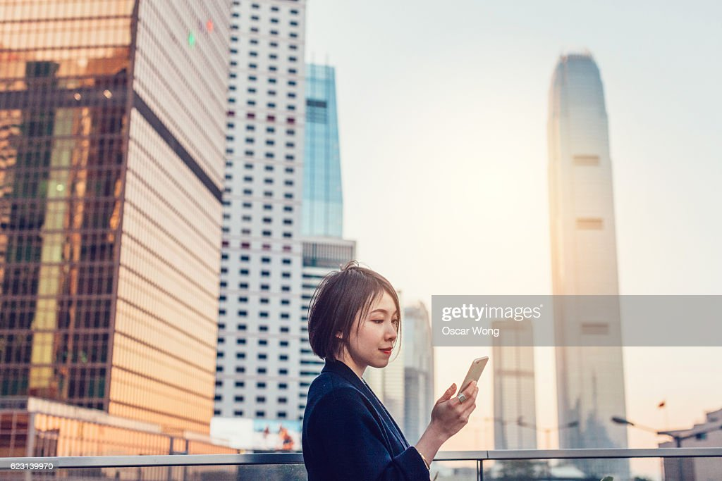 Young woman reading email on phone : Stock Photo