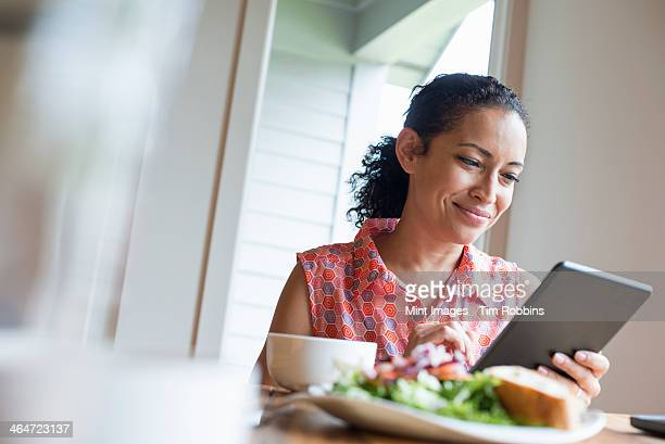 A young woman reading from the screen of a digital tablet,seated at a table. Coffee and a sandwich.