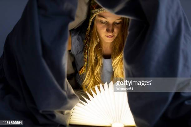 young woman reading illuminated book in bed at home - rechtschreibung stock-fotos und bilder