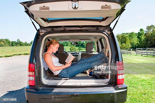 Young woman reading in back of sports utility vehicle