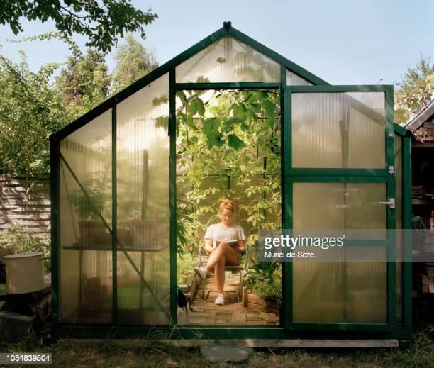young woman reading in green house - gewächshäuser stock-fotos und bilder