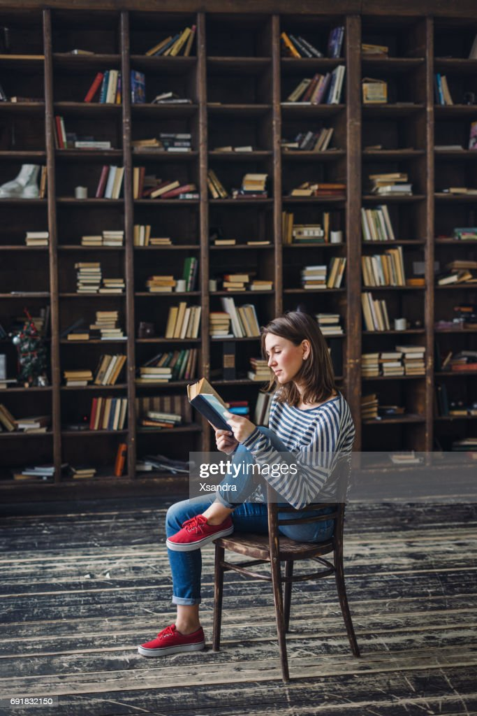 Young woman reading in the library : Stock Photo