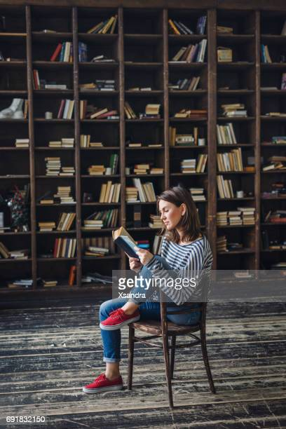 young woman reading in the library - book imagens e fotografias de stock