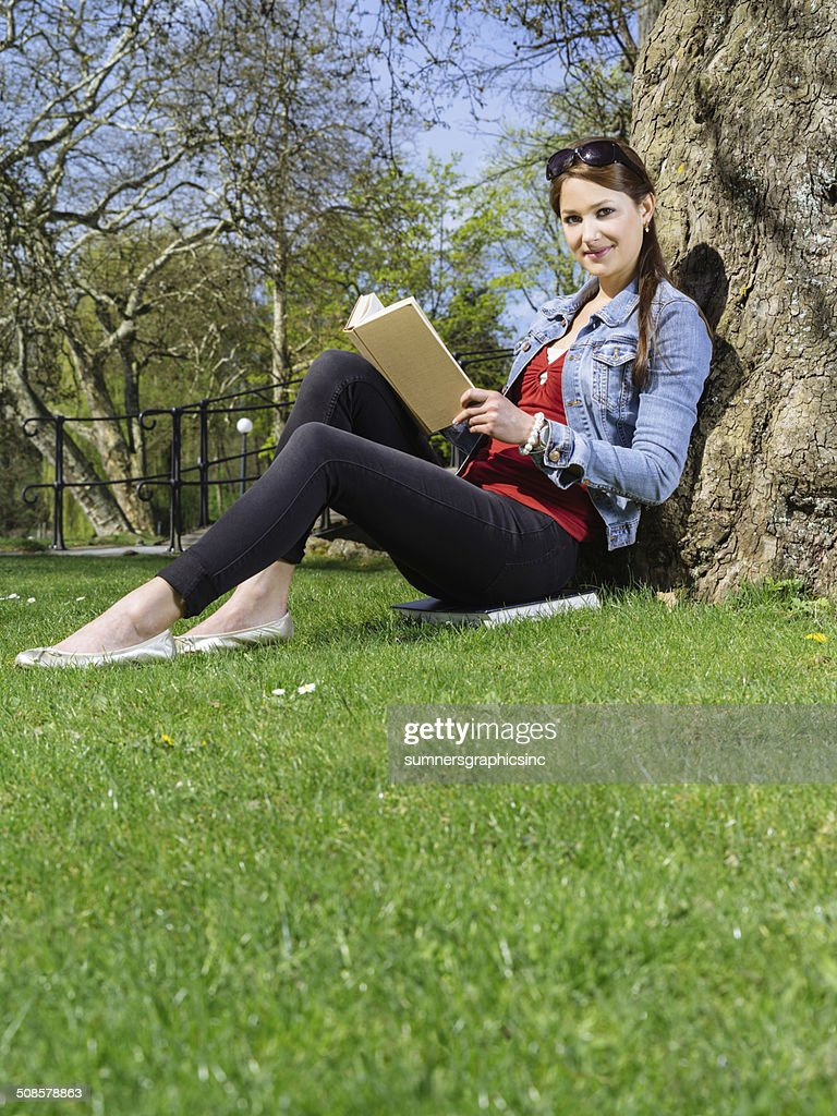 Young woman reading in the park : Stock Photo