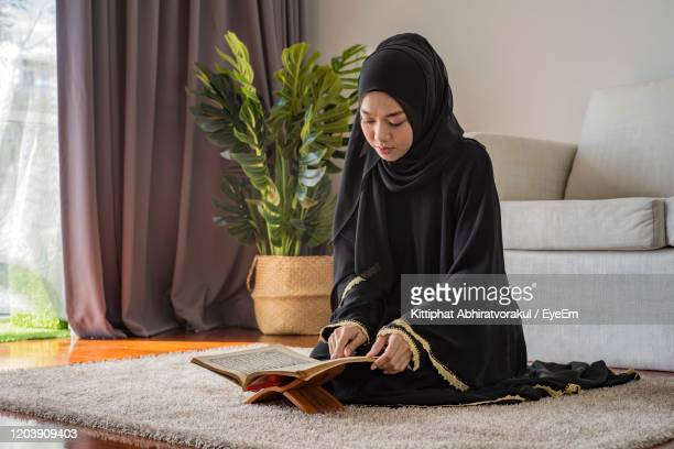 young woman reading koran while sitting on floor at home - koran stock pictures, royalty-free photos & images