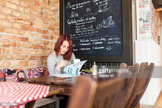 Young woman reading magazine at cafeteria