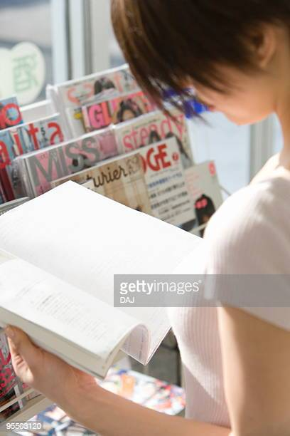 Young woman reading magazine at convenience store