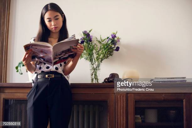 Young woman reading magazine at home