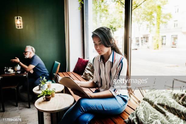 young woman reading magazine at local coffee shop - nur erwachsene stock-fotos und bilder