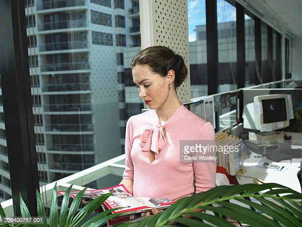 Young woman reading magazine by window in office