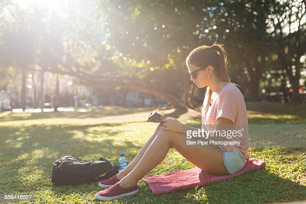 Young woman reading magazine in park, Manila, Philippines