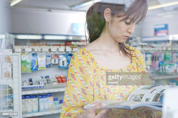 Young woman reading magazine in store