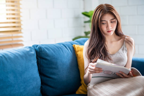 Young Woman Reading Magazine While Sitting On Sofa At Home