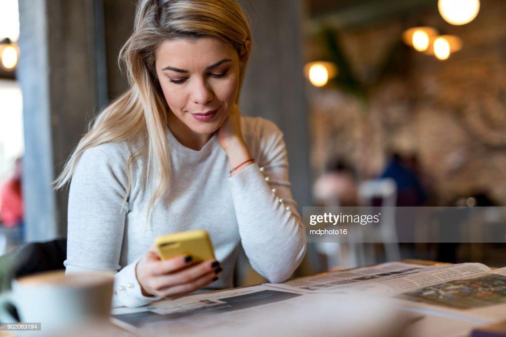 Junge Frau, lesen Zeitung und SMS in Coffee-shop : Stock-Foto