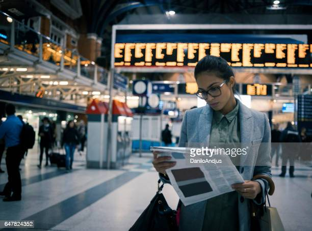 young woman reading newspaper at the station - newspaper stock pictures, royalty-free photos & images