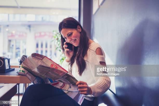 young woman, reading newspapers, sitting in cafe. - publication stock pictures, royalty-free photos & images