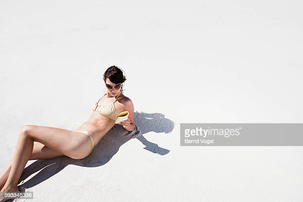 Young woman reading on a beach