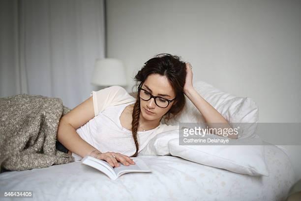 a young woman reading on her bed - lunettes de lecture photos et images de collection