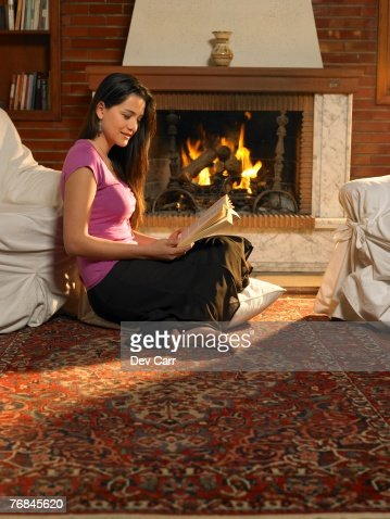 Young Woman Reading On Rug In Front Of Fire Alicante Spain